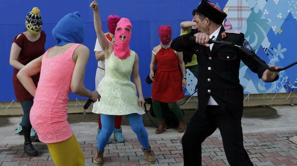 Members of the punk group Pussy Riot, including Nadezhda Tolokonnikova in the blue balaclava and Maria Alekhina in the pink balaclava, are attacked by Cossack militia in Sochi, Russia on Feb. 19, 2014. The incident occurred outside a downtown Sochi restaurant, about 21 miles from where the Winter Olympics are being held.